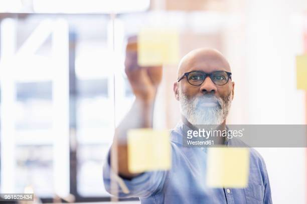 portrait of businessman taking adhesive note from glass wall in office - effektivität stock-fotos und bilder