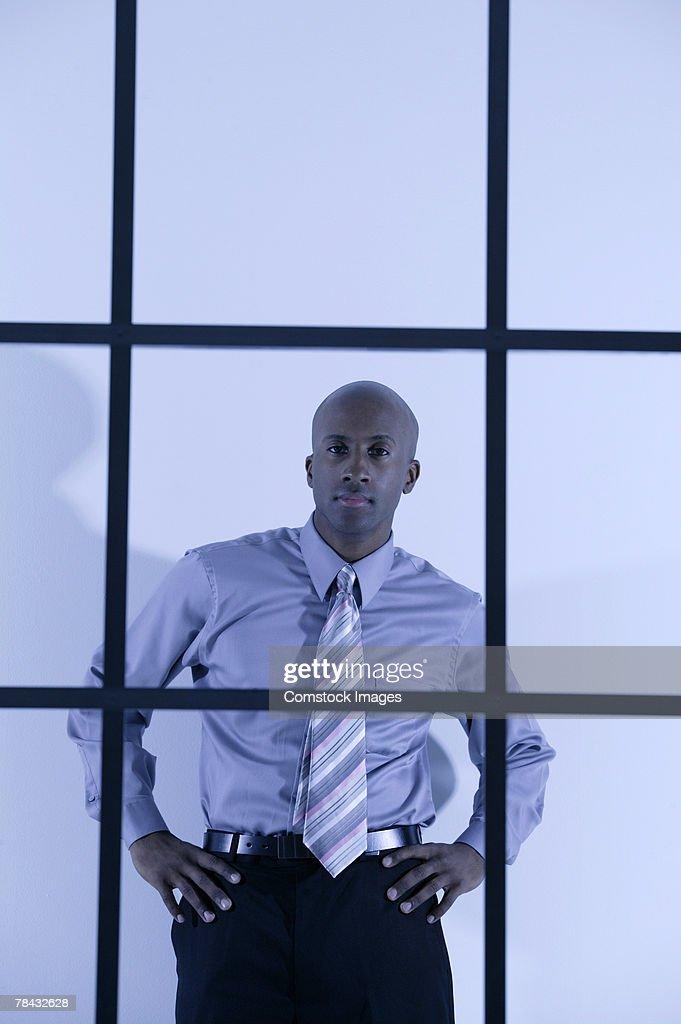 Portrait of businessman through window bars : Stockfoto