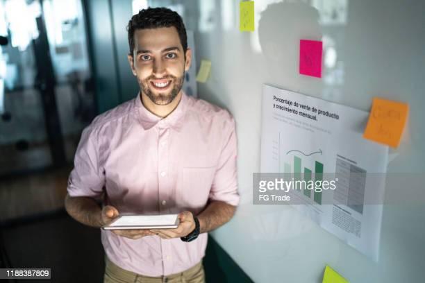 portrait of businessman using digital tablet - pardo brazilian stock pictures, royalty-free photos & images