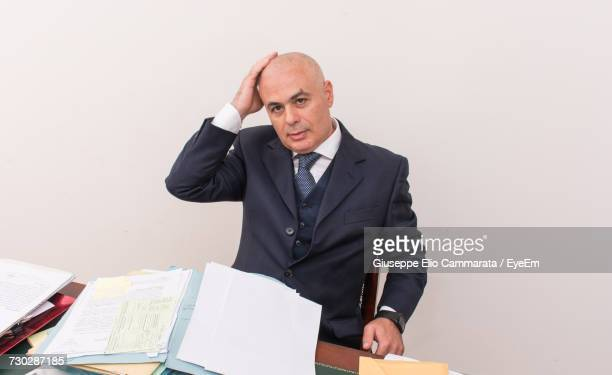 Portrait Of Businessman Using Laptop At Office