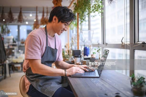 portret van zakenman met behulp van laptop in de winkel - eigenaar stockfoto's en -beelden