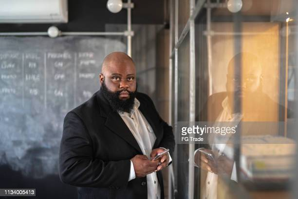 portrait of businessman using mobile at creative office - fat bald men stock pictures, royalty-free photos & images