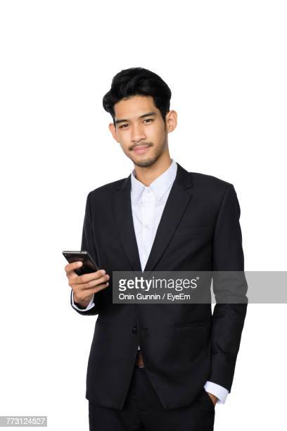 Portrait Of Businessman Using Phone Against White Background
