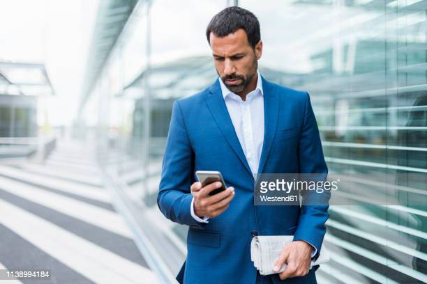 portrait of businessman using smartphone - blue suit stock pictures, royalty-free photos & images