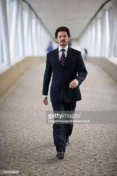 Portrait of businessman walking down corridor