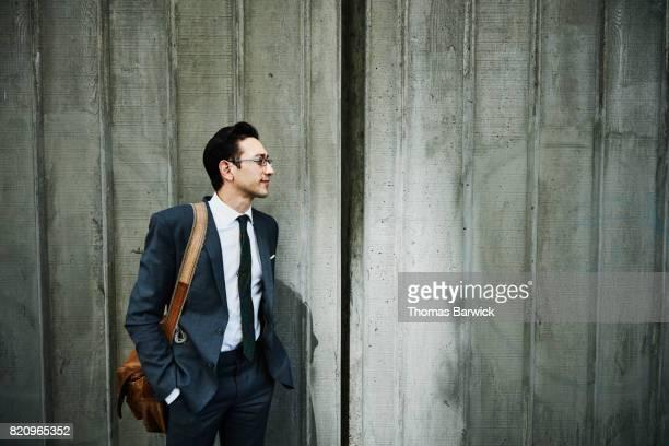Portrait of businessman walking on city sidewalk
