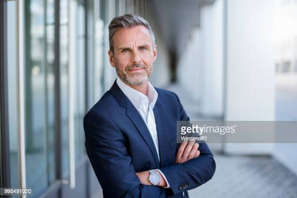portrait of businessman wearing blue suit coat and wrist watch - oberkörperaufnahme stock-fotos und bilder