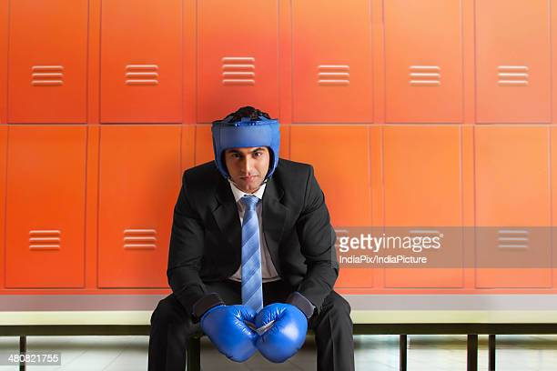 Portrait of businessman wearing boxing gloves sitting on bench in locker room