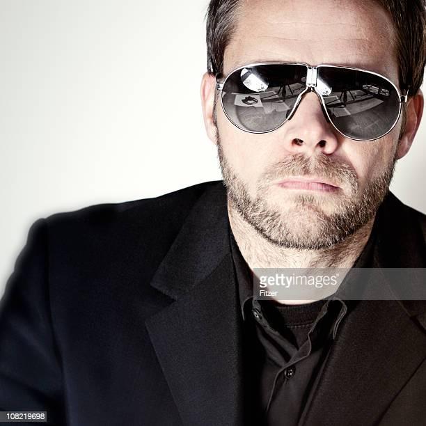 Porträt der Geschäftsmann mit Sonnenbrille vor einem weißen Hintergrund.
