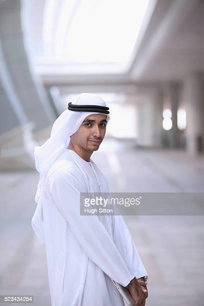 portrait of businessman wearing traditional clothing holding laptop - hugh sitton stock-fotos und bilder