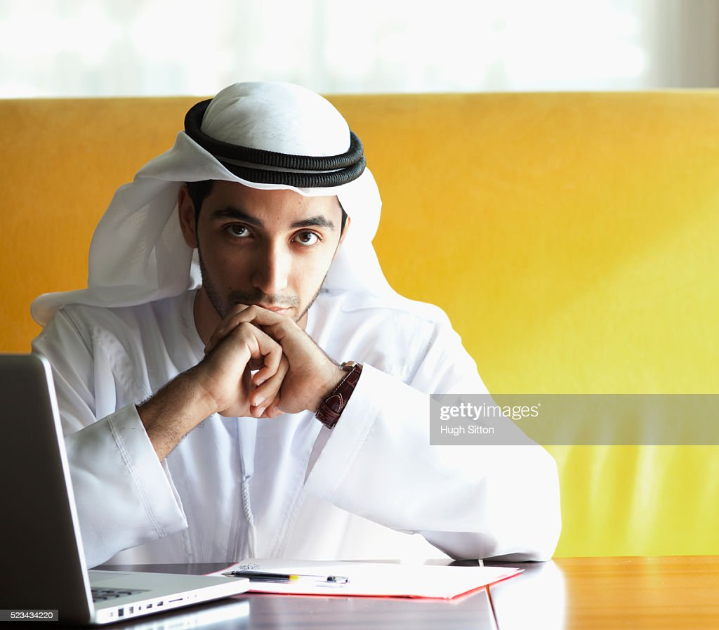 Portrait of businessman wearing traditional clothing sitting at desk with laptop : Stock Photo