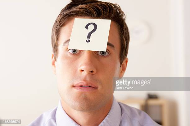 Portrait of businessman with adhesive note attached on forehead