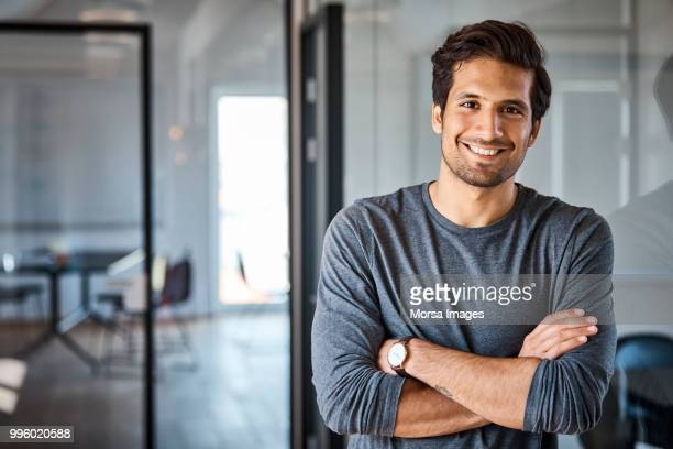 portrait of businessman with arms crossed - latino américain photos et images de collection