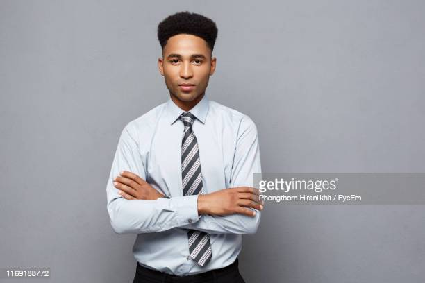 portrait of businessman with arms crossed standing against gray background - overhemd en stropdas stockfoto's en -beelden
