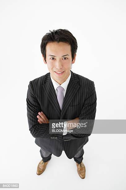 Portrait of businessman with arms folded, high angle view, studio shot
