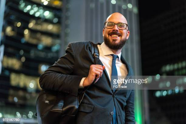 portrait of businessman with city lights on background - economist stock pictures, royalty-free photos & images