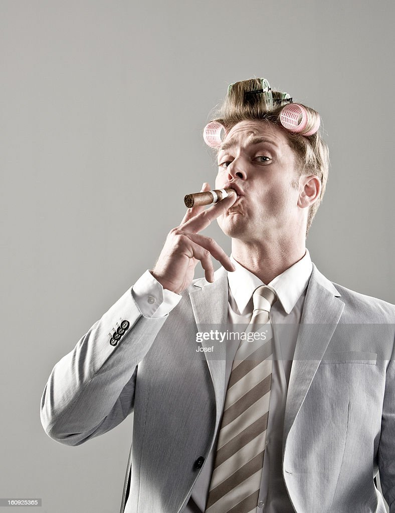 portrait of businessman with curlers in hair and smoking cigar : Stock Photo