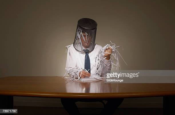 portrait of businessman with empty wastebasket over his head