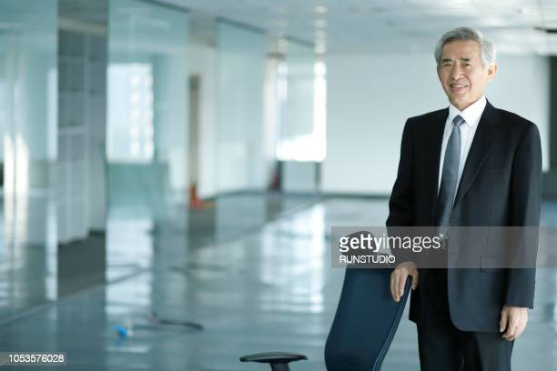 portrait of businessman with hand on chair - 最高経営責任者 ストックフォトと画像