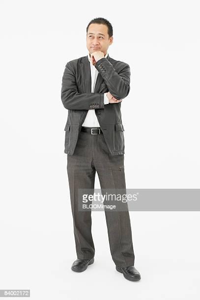 Portrait of businessman with hand on chin, studio shot