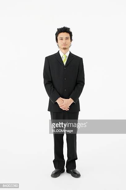 Portrait of businessman with hands clasped, studio shot