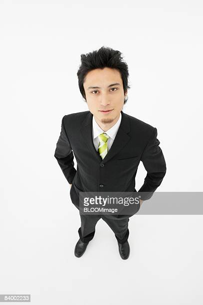 Portrait of businessman with hands in pockets, high angle view, studio shot