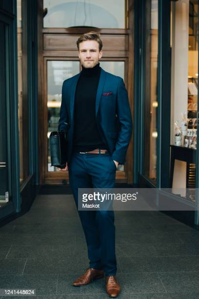 portrait of businessman with hands in pockets standing by store in city - double breasted stock pictures, royalty-free photos & images