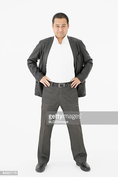 Portrait of businessman with hands on hips, studio shot