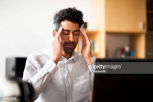 Portrait of businessman with hands on his temples at desk in office