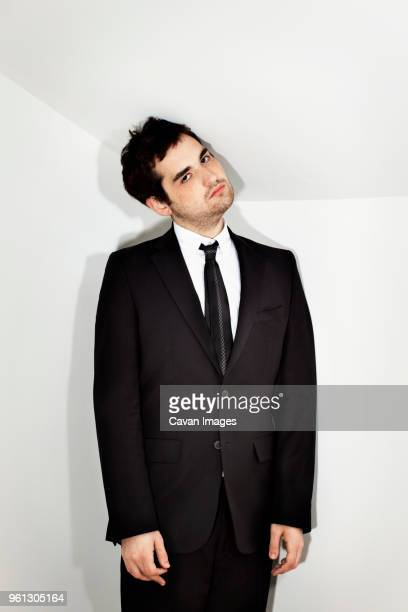 portrait of businessman with head cocked standing against white wall - head cocked stock pictures, royalty-free photos & images