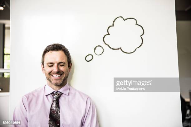 Portrait of businessman with idea bubble