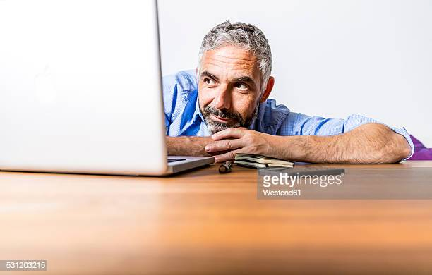 Portrait of businessman with laptop at home office