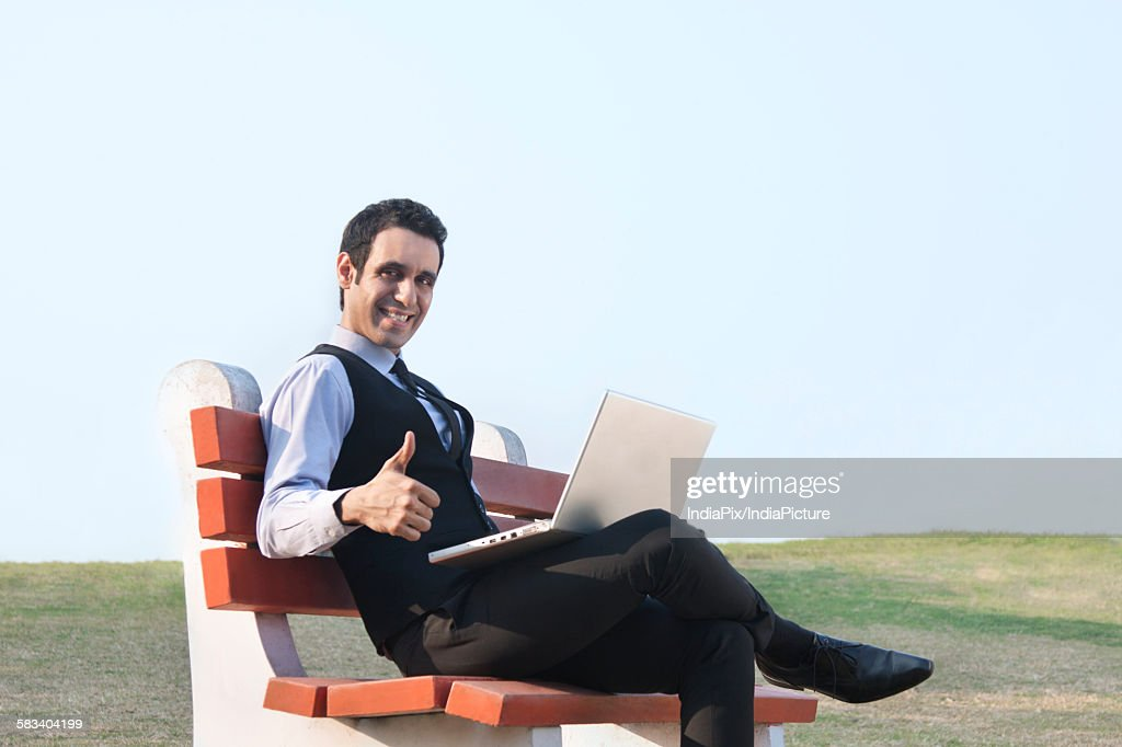 Portrait of businessman with laptop giving thumbs up , INDIA , DELHI : Stock Photo