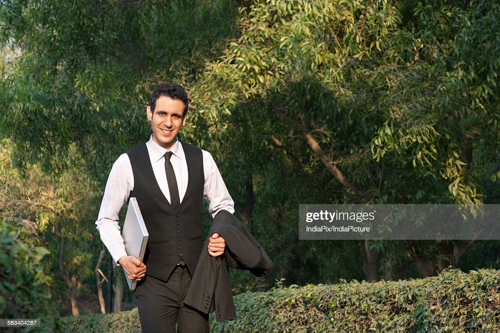 Portrait of businessman with laptop smiling , INDIA , DELHI : Stock Photo