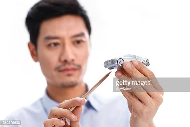 Portrait of businessman with model car