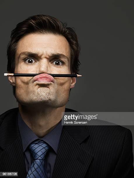 Portrait of businessman with pencil above lip