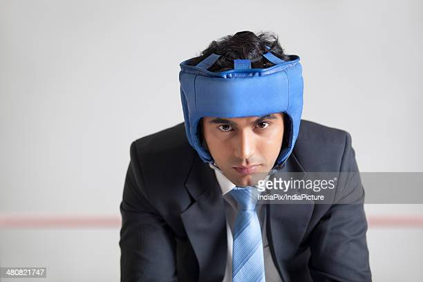 Portrait of businessman with protective headgear in boxing ring