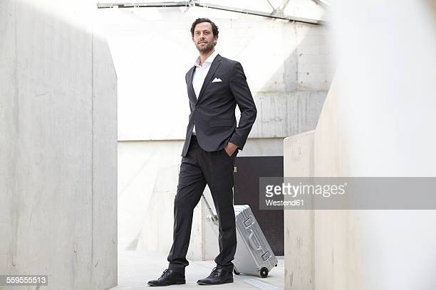 Portrait of businessman with rolling suitcase in a modern building