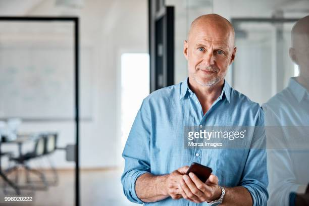 portrait of businessman with smart phone at office - completely bald stock pictures, royalty-free photos & images