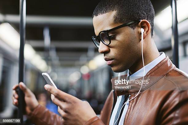 Portrait of businessman with smartphone and earphones hearing music on the subway train