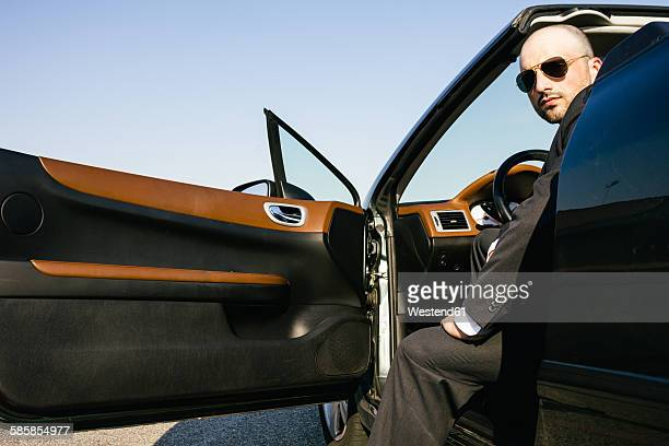Portrait of businessman with sunglasses sitting on driver seat of a convertible car