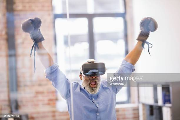 portrait of businessman with virtual reality glasses and boxing gloves in the office - boxeo deporte fotografías e imágenes de stock