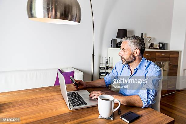 portrait of businessman working with laptop at home office - wood table top stock photos and pictures