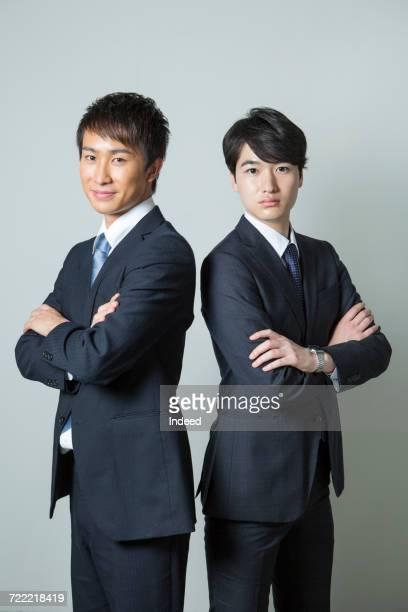 portrait of businessmen crossing arms - 背中合わせ ストックフォトと画像