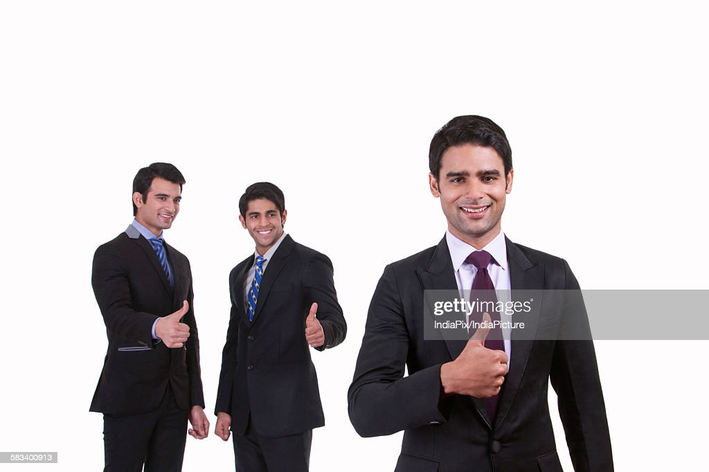 Portrait of businessmen giving thumbs up : Stock Photo
