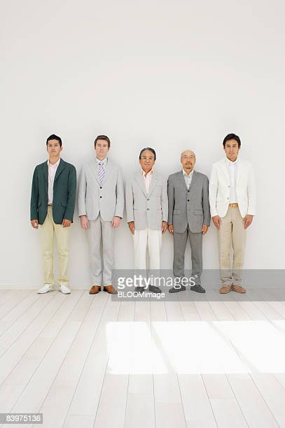 portrait of businessmen standing in row against wall - 連続 ストックフォトと画像