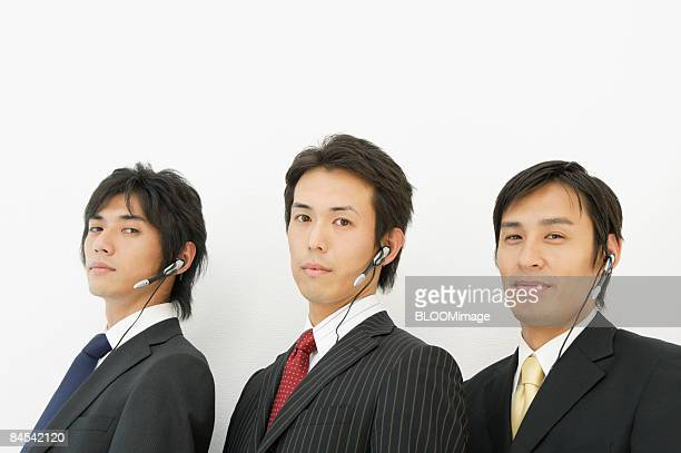 Portrait of businessmen with headsets, close-up
