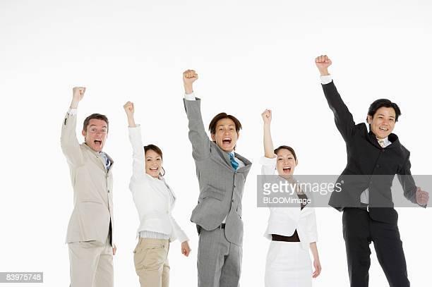 Portrait of businesspeople raising fists, studio shot