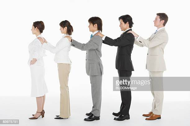 Portrait of businesspeople standing in line, putting hands on shoulders of person ahead, side view, studio shot