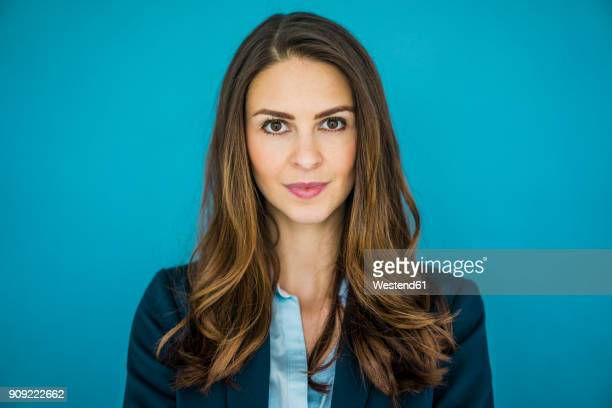 portrait of businesswoman against blue background - braune augen stock-fotos und bilder